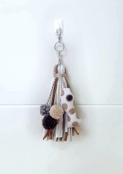 Llavero, colgante o adorno de trapillo con pez de tela en tonos beige.