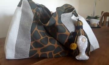 Enorme bolso de tela en tonos ocres con adorno