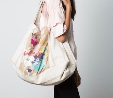 Bolso de tela base beige con detalles en flores tonos pasteles. Modelo big bag.