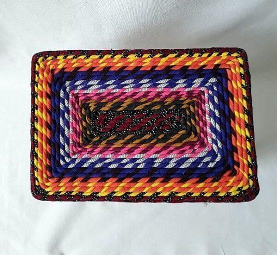 Taburete de madera con base rectangular forrado en tela y trapillo en tonos cálidos.