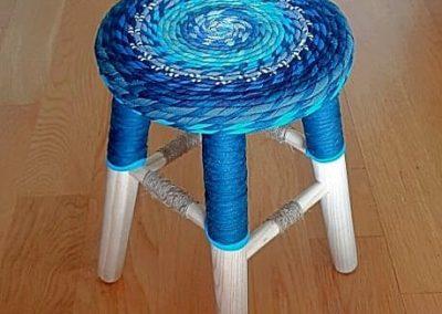 Taburete bajo circular en tonos fríos. Azules