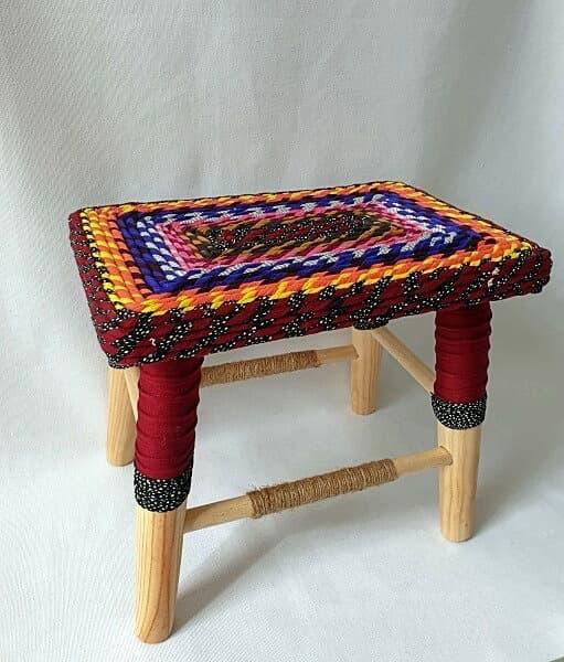 Banco, taburete o asiento de madera forrado en telas de colores cálidos